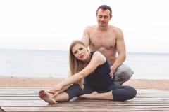 Человек и беременная женщина делают йогу на пляже Стоковое Изображение RF
