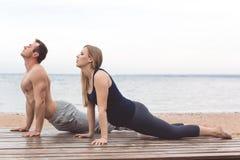 Человек и беременная женщина делают йогу на пляже Стоковые Изображения RF