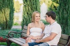 Человек и беременные женщины сидя на стенде в парке Стоковые Изображения RF