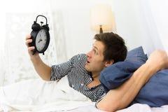 Человек и будильник в кровати Стоковые Изображения RF