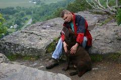Человек и верноподданическая собака на горном пике Стоковое Изображение RF