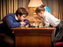 Человек и девушка играя классический шахмат Стоковое Изображение RF