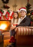 Человек и девушка ослабляя на софе на камине на Рожденственской ночи Стоковое Изображение