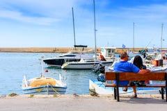 Человек и девушка сидят на стенде в порте и ждут девушку против предпосылки белых яхт и шлюпок Стоковые Изображения RF
