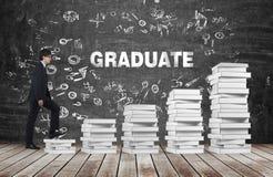 Человек идет вверх использовать лестницы которые сделаны из белых книг Студент-выпускник слова на черной доске Стоковая Фотография RF