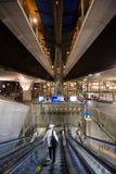 Человек идет вниз на эскалатор на железнодорожном вокзале Стоковые Изображения
