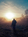 Человек идет против восхода солнца Стоковые Изображения