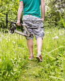 Человек идет согласовывать след леса и носит внутри ее самокат руки, Стоковое фото RF