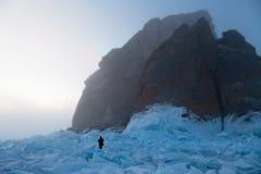 Человек идет среди голубого льда вокруг вычисляемых утесов в тумане Стоковые Изображения RF