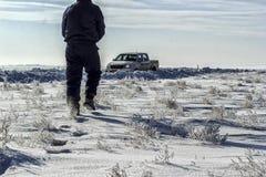 Человек идет через снег стоковые изображения rf
