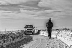 Человек идет через снег Стоковое фото RF