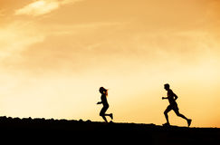 Человек и женщина бежать совместно в заход солнца Стоковое Фото