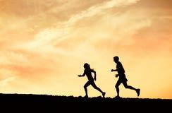 Человек и женщина бежать совместно в заход солнца Стоковые Фото