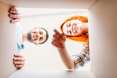 Человек и женщина, взгляд изнутри картонной коробки Стоковые Изображения