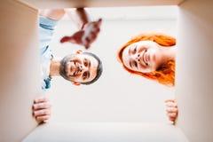 Человек и женщина, взгляд изнутри картонной коробки Стоковое Изображение RF
