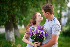Человек и женщина встречают в парке с пуком цветков Стоковые Изображения