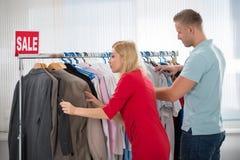 Человек и женщина выбирая одежды в магазине Стоковые Фото