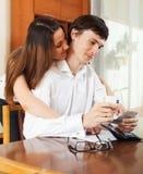 Человек и женщина высчитывая бюджет Стоковые Изображения