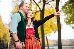 Человек и женщина в баварском Tracht, указывать девушки стоковое фото rf