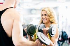 Человек и женщина в гантелях спортзала фитнеса поднимаясь Стоковые Фотографии RF