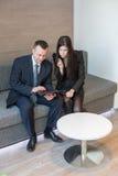 Человек и женщина в деловых костюмах сидя на софе Стоковые Фото