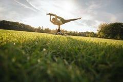 Человек и женщина в йоге пар парка практикуя Стоковые Фотографии RF