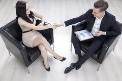 Человек и женщина в креслах тряся руки Стоковые Изображения