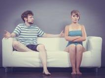 Человек и женщина в разногласии сидя на софе Стоковые Фотографии RF