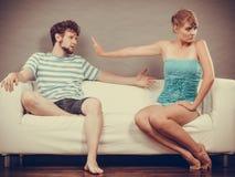 Человек и женщина в разногласии сидя на софе Стоковые Изображения RF