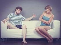 Человек и женщина в разногласии сидя на софе Стоковое фото RF
