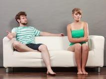 Человек и женщина в разногласии сидя на софе Стоковая Фотография