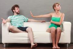 Человек и женщина в разногласии сидя на софе Стоковые Фото