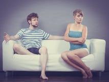 Человек и женщина в разногласии сидя на софе Стоковая Фотография RF