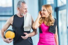 Человек и женщина в sportswear с полотенцами на одине другого плеч усмехаясь Стоковое фото RF
