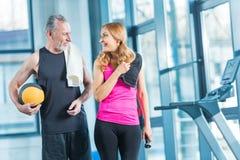 Человек и женщина в sportswear с полотенцами на одине другого плеч усмехаясь Стоковая Фотография RF