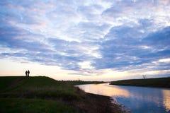 Человек и женщина говорят на заходе солнца на банках реки Стоковое Фото
