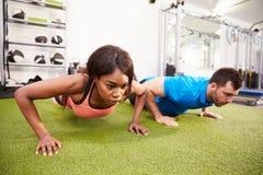 Человек и женщина делать нажимает поднимают на спортзале Стоковая Фотография