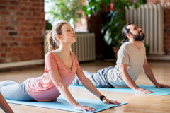 Человек и женщина делая кобру йоги представляют на студии Стоковые Фото