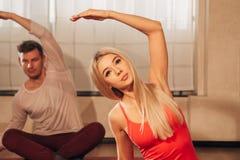 Человек и женщина делая тренировки йоги стоковое изображение
