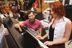 Человек и женщина играя рояль на магазине музыки Стоковые Изображения
