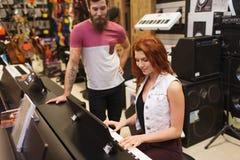 Человек и женщина играя рояль на магазине музыки Стоковая Фотография