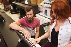 Человек и женщина играя рояль на магазине музыки Стоковое Фото