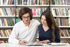 Человек и женщина изучая и работая в библиотеке Стоковые Изображения
