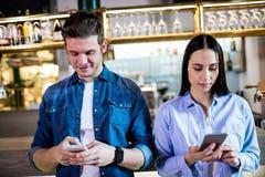Человек и женщина используя мобильный телефон в баре Стоковая Фотография RF