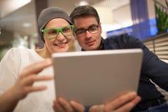 Человек и женщина используя электронную таблетку в Стоковое Фото
