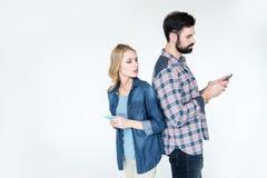 Человек и женщина используя smartphones и положение спина к спине Стоковое фото RF