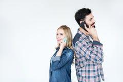 Человек и женщина используя smartphones и положение спина к спине Стоковые Изображения