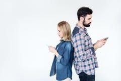 Человек и женщина используя smartphones и положение спина к спине Стоковая Фотография RF