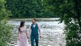 Человек и женщина, молодая счастливая пожененная пара около озера акции видеоматериалы