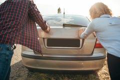 Человек и женщина нажимая сломленный автомобиль, задний взгляд Стоковое Фото